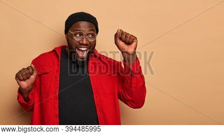 Energized Dark Skinned African American Man Raises Clenched Fists, Dances With Triumph, Has Fun Alon