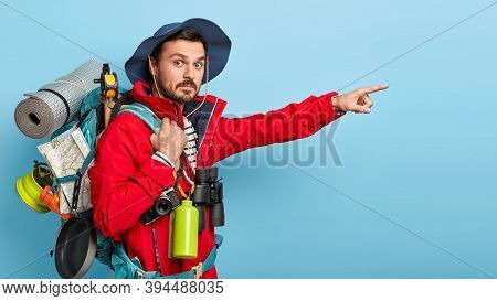 Sideways Shot Of Surprised Man Wears Hat And Casual Clothes, Points Away With Index Fingers, Carries