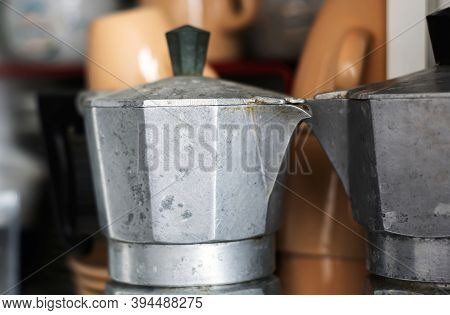 Close-up View Of An Old Rusty Coffee Pot Inside A Pantry. Scratches And Signs Of Wear Near The Spout