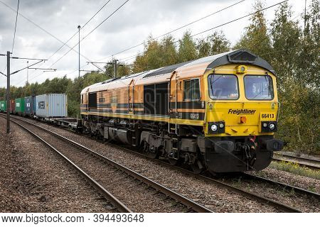 Doncaster, Uk - October 15, 2020. A Freightliner Class 66 Locomotive And Intermodal Shipping Contain