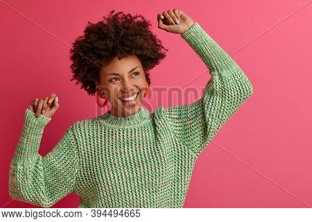 Energetic Carefree Dark Skinned Millennial Woman Makes Victory Dance, Celebrates Something, Feels Ve