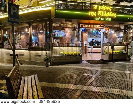 Thessaloniki, Greece - November 9 2020: Hellenic empty open restaurant without crowd. Illuminated night view of grill shop only accepting orders for take away & deliveries, due to covid-19 measures.