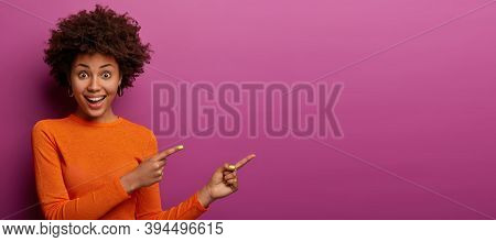 Happy Reaction On Advert. Positive Excited Woman Has Afro Hairstyle, Dressed In Orange Jumper, Has W