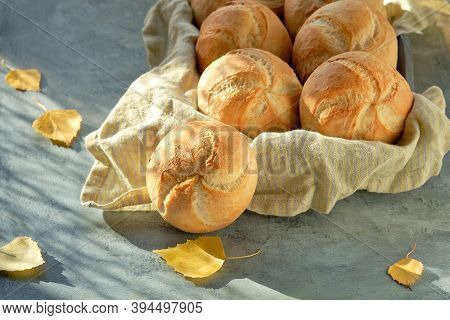 Kaiser, Or Vienna Buns In Bread Basket On Dark Textured Background With Yellow Autumn Leaves.