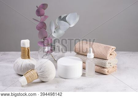 Set Of Massage Bags With Herbs, Cream And Towels In Light Colors
