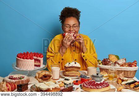Cheat Meal And Gluttony Concept. Ethnic Curly Woman Eats Strawberry Creamy Cake With Much Calories,