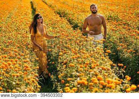 Couple In Love On A Flower Field. A Beautiful Couple Runs Through A Flower Field. Man And Woman In T