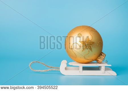 Close Up Side Profile View Photo Of Decorated Golden Bauble On Little White Wooden Sledge Isolated O
