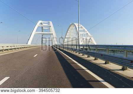 New Asphalt Road Over The Bridge Over The Kerch Strait. White Arches Of Unsupported Span Of Automobi