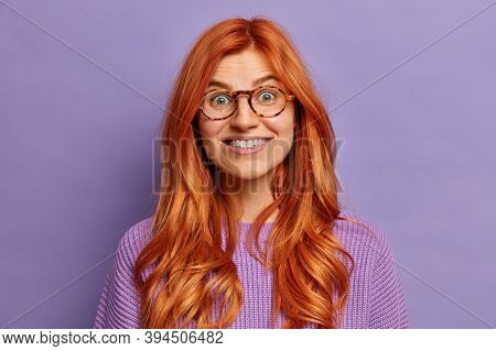 Portrait Of Pretty Cheerful Redhead Woman Smiles Broadly, Looks Curiously At Camera And Dressed In P