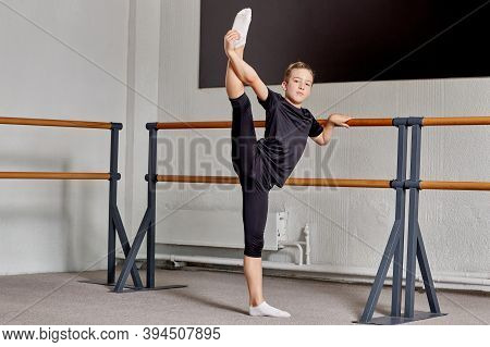 A Man Does Stretching Exercises At A Sports School. The Leg Is Raised High Up.