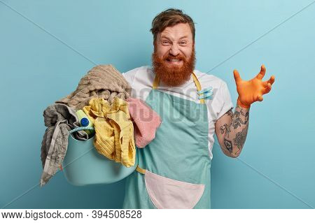 Distraught Bearded Man Holds Laundry Basket, Overwhelmed By Household Chores, Gestures Angrily, Wear