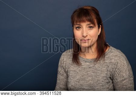 Serious Woman In Her Thirties Lady Studio Portrait Spokesperson On Blue Background