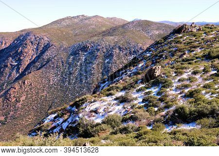 Mountains With Windswept Ridges And Snow Surrounded By Chaparral Shrubs Taken In The Rural Southern