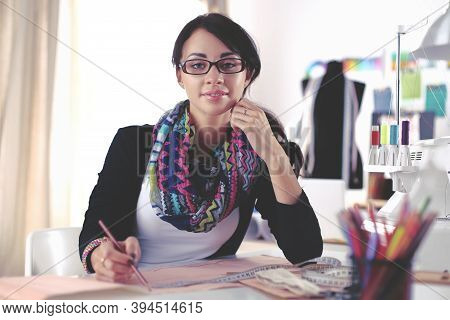 Dressmaker Woman Designing Clothes Pattern On Paper