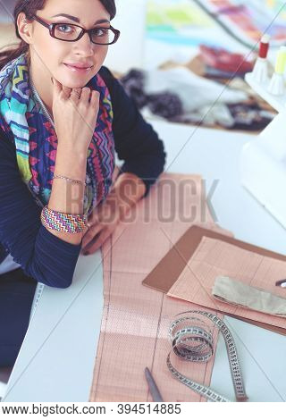 Young Dressmaker Designing Clothes Pattern On Paper