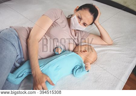 Young Mother In Protective Face Mask With A Newborn Cute Infant Baby In Blue Jumpsuit, Hugging And B