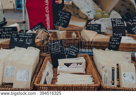 Frome, Uk - October 07, 2020: Variety Of Local Cheeses In Baskets On Sale At A Street Market In From