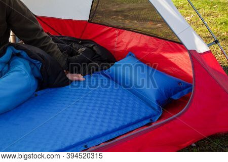 A Man Gets His Tent And Sleeping Bag Ready At A Campground By Inflating And Setting Up His Blue Blow