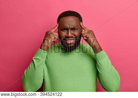 Photo Of Intense Bearded Man Worker Suffers From Headache Because Of Long Hours Of Working, Keeps In