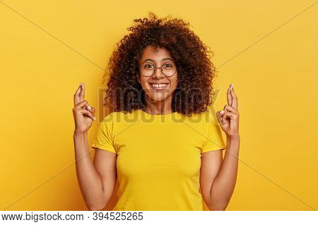 Attractive Woman In Yellow T Shirt, Crosses Fingers, Believes Dreams Come True, Hopes In Lucky Futur
