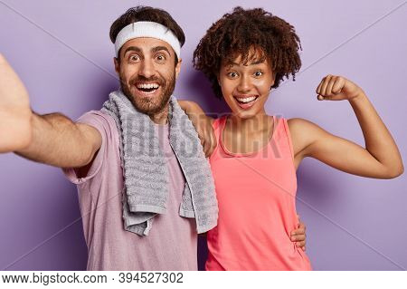Indoor Shot Of Joyful Diverse Couple Keep Muscle Flexible, Live Healthy Life, Have Daily Workout, We