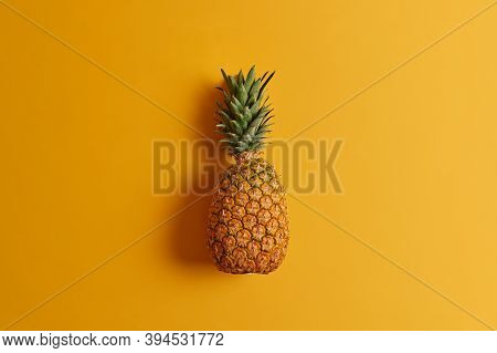 Ripe Pineapple Isolated On Yellow Background. Exotic Fruit Low In Calories, Loaded With Nutrients An