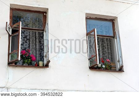 Rustic House With White Washed Walls And Open Windows. Blooming Potted Flowers On Sills. Summer Cott