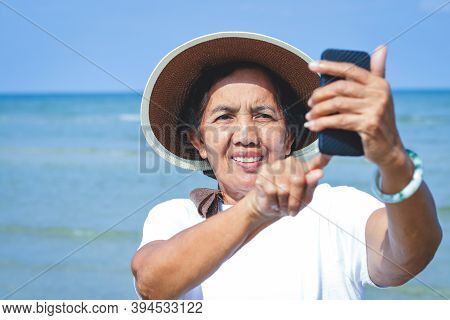 Elderly Women Travel To The Sea, Smiling, Happy, Holding A Phone, Taking Pictures Of Themselves.