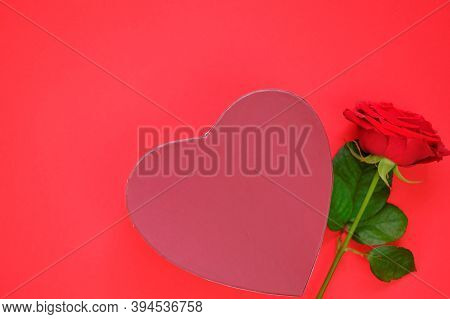 Valentine's Day Holiday. Red Rose Flower And Box In The Shape Of A Heart On A Bright Red Background.