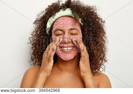 Image Of Happy Pretty African American Woman Makes Peeling Of Face With Pink Sea Salt Scrub, Touches