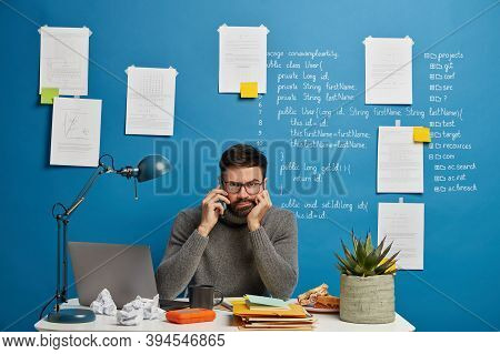 Having Important Conversation. Serious Bearded Male Worker Sits At Desktop And Talks Via Cell Phone,