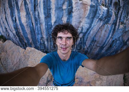A Man Takes A Selfie Against A Background Of Beautiful Blue Rocks, A Man Travels To Picturesque Plac