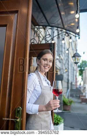 Smiling Cute Waitress In Grey Apron Holding Glass Of Wine