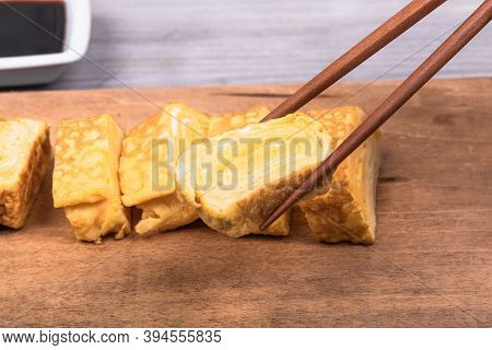 Tamago Japanese Omelet On A Wooden Serving Board And Chopsticks Hold A Piece Of Omelet, Close-up