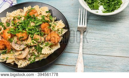 Farfalle With Cream Sauce With Calamari And Mushrooms And Fried Shrimps In A Black Plate - Tradition