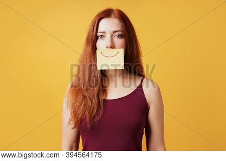 Young Woman Hiding Sadness Or Depression Behind Fake Smile Drawn On Yellow Sticky Note Paper