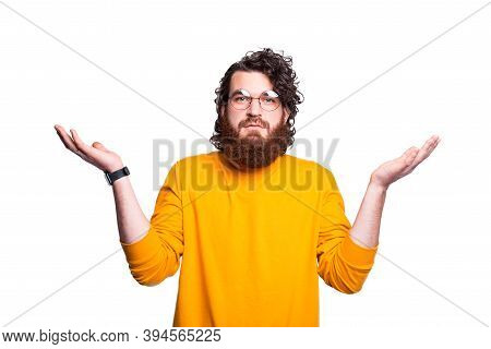 An Unsure Young Bearded Man With Glasses Is Showing Dont Know Gesture On A White Wall