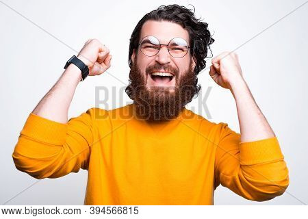 An Excited Bearded Man With Glasses Is Screaming Of Happiness
