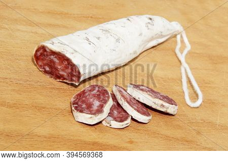 Close-up Italian And Catalonia Fuet Cured Pork Sausage With Slices On Wooden Table. Sausage From Min
