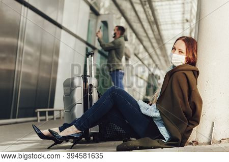 Young Woman In Medical Mask Sits Near Luggage In Airport. Tortured By The Flight, The Woman Dozes Of