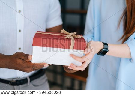 Close-up View Of Woman Giving Gift Box To Colleague At Office. Cheerful Business Team Of Multiethnic
