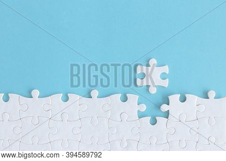 Assembling Jigsaw Puzzle Pieces, Top View Unfinished White Jigsaw Puzzle On Blue Background, Fragmen