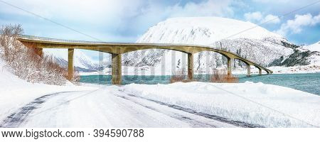 Dramatic  Winter Scene Of Gimsoystraumen Bridge With Lots Of Snow  And Snowy  Mountain Peaks.  Locat