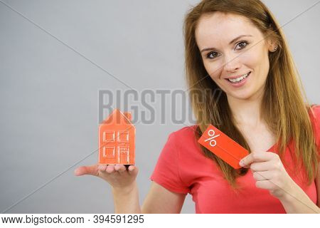 Woman Is Happy About Buying House In Affordable Price. Female Holding Small Red Home Model And Sale