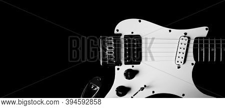 Part Of Body Electric Guitar On A Black Background, Copy Space. Black And White Guitar Close Up. Cre