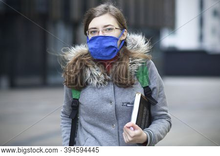 Young Woman, University Or College Student Girl In Protective Mask On Her Face And In Glasses Holdin
