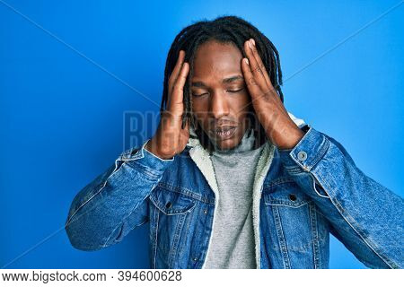 African american man with braids wearing casual denim jacket suffering from headache desperate and stressed because pain and migraine. hands on head.