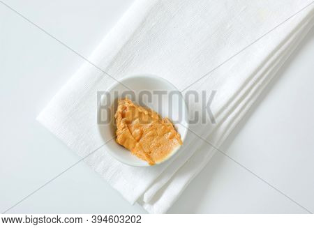 Bowl of crunchy peanut butter on white napkin