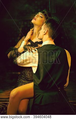 Beautiful couple are in a passionate embrace of each other in a richly furnished room. Fashion clothes, make-up and hair in the style of 1920s.